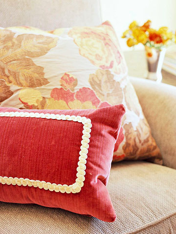 red and yellow throw pillows on a beige sofa