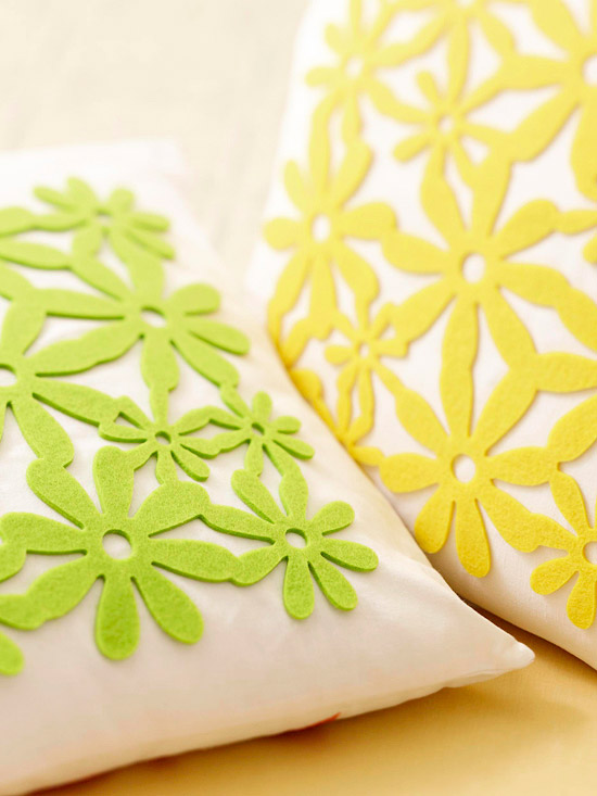 Pale green and yellow felt flower patterns adorn plain white pillows.