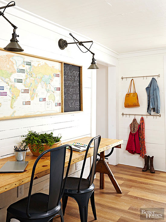 Rustic home office with shiplap walls and swing-arm sconces for task lighting. From Better Homes and Gardens.