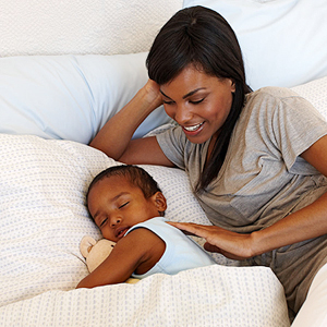 mother putting child to bed