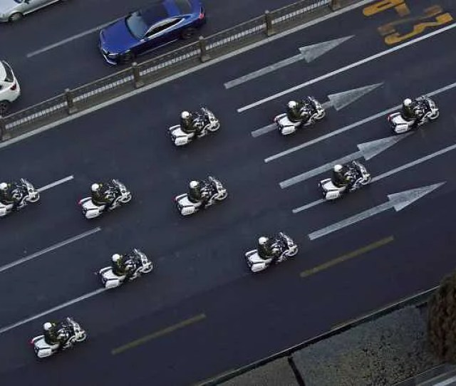 Chinese Paramilitary Policemen On Motorcycles Escort A Motorcade Believed To Be Carrying North Korean Leader Kim Jong Un Traveling Past Changan Avenue In