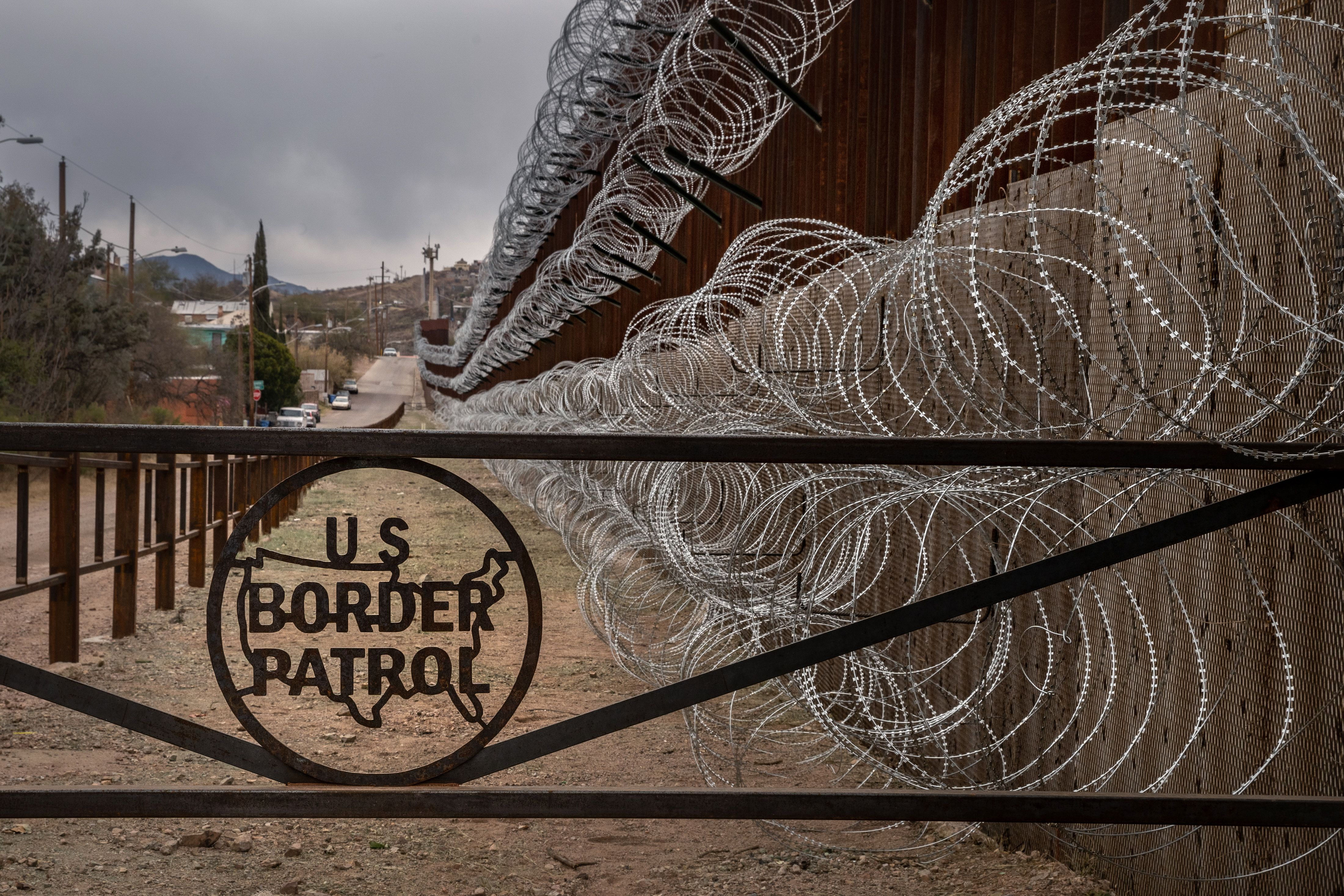 A barbed wire fence marked with the US Border Patrol sign at the US-Mexico border in Nogales, Arizona