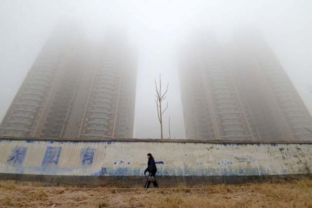 A woman wearing a mask walks past buildings on a polluted day in Handan, Hebei province, China January 12, 2019. REUTERS/Stringer/Files