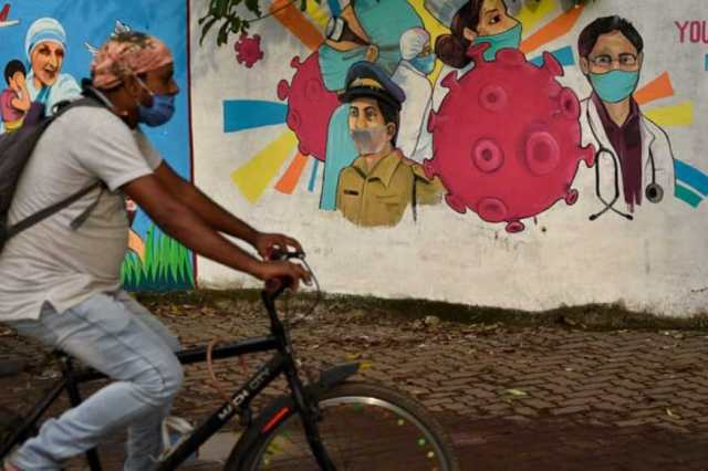 A man wearing a mask pedals his bicycle past a graffiti on a wall made to create awareness about the coronavirus. (AP)