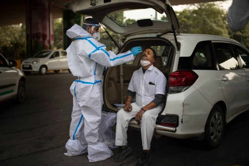 A health worker takes a nasal swab sample of a man to test for COVID-19 during random testing of people at the Delhi-Noida border on the outskirts of New Delhi. (AP)