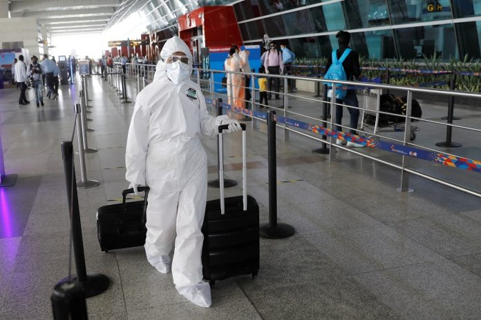 A person wearing personal protective equipment (PPE) carries luggage at Indira Gandhi International (IGI) airport in New Delhi. (Reuters)