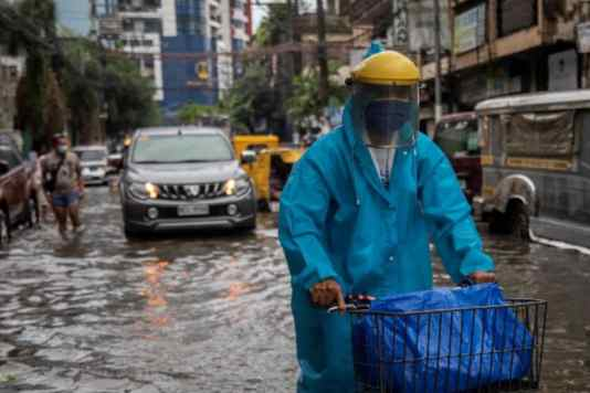 PHILIPPINES: A man wearing a face shield for protection against the coronavirus disease (COVID-19) rides a bicycle on a flooded street in Manila, Philippines. (Image: REUTERS)