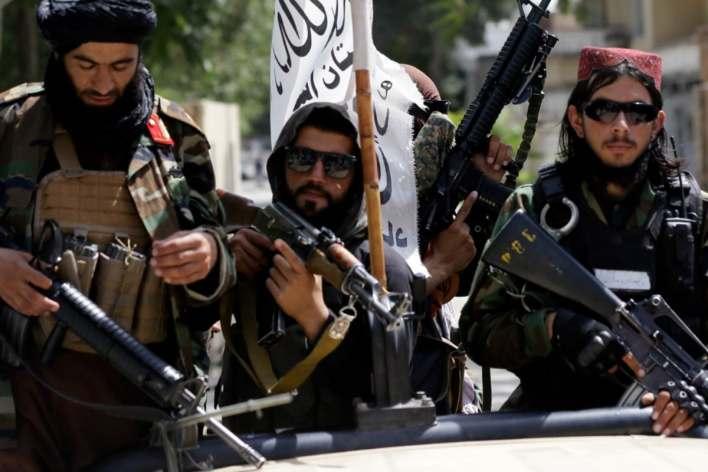 Taliban fighters display their flag on patrol in Kabul, Afghanistan.(AP Photo)