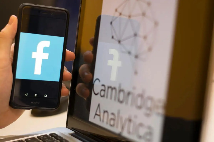 A picture of Facebook on a phone with Cambridge Analytica in the background