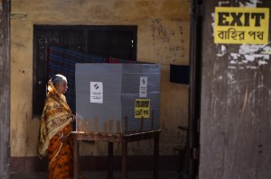 A woman votes in a booth at a polling station during India's general election in Cooch Behar, West Bengal on April 11, 2019