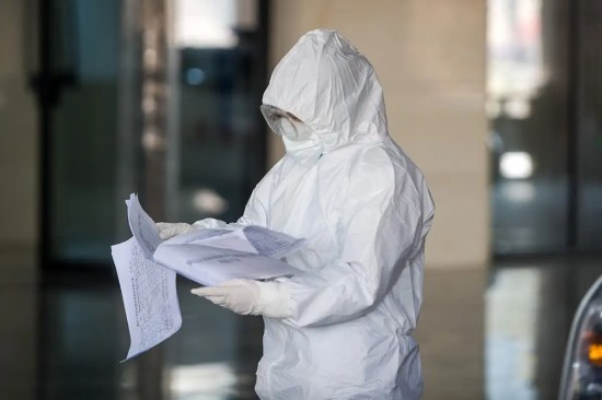 A person in a hazmat suit reads a piece of paper