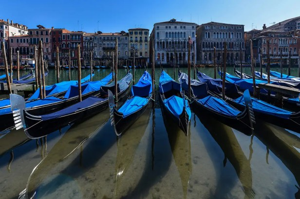 TOPSHOT - A view shows clear waters by gondolas in Venice's Grand Canal on March 18, 2020 as a result of the stoppage of motorboat traffic, following the country's lockdown within the new coronavirus crisis. (Photo by ANDREA PATTARO / AFP) (Photo by ANDREA PATTARO/AFP via Getty Images)