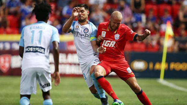 Adelaide defender Taylor Regan challenges for the ball with City striker Bruno Fornaroli.