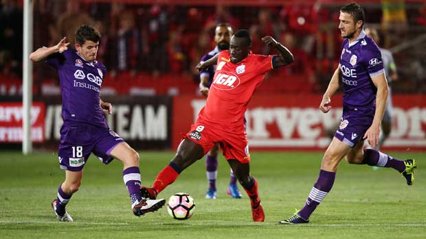 Adelaide United striker Baba Diawara looks to get between two Perth Glory defenders.