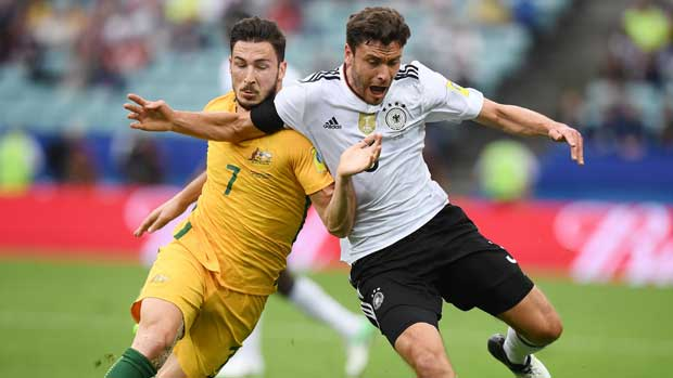 Caltex Socceroos winger Mat Leckie battles hard for possession with a German defender.