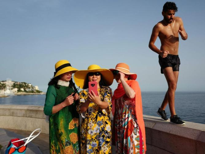 Tourists in the French Riviera city of Nice cover up against the sun.