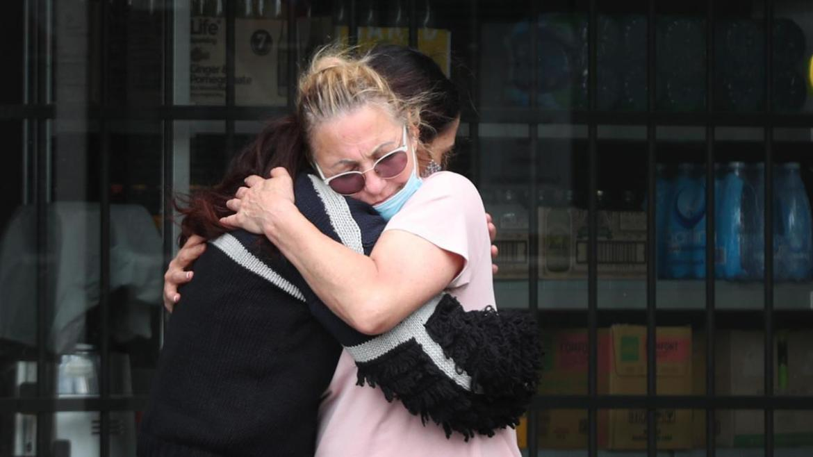 A mother and daughter hug waiting in the queue.