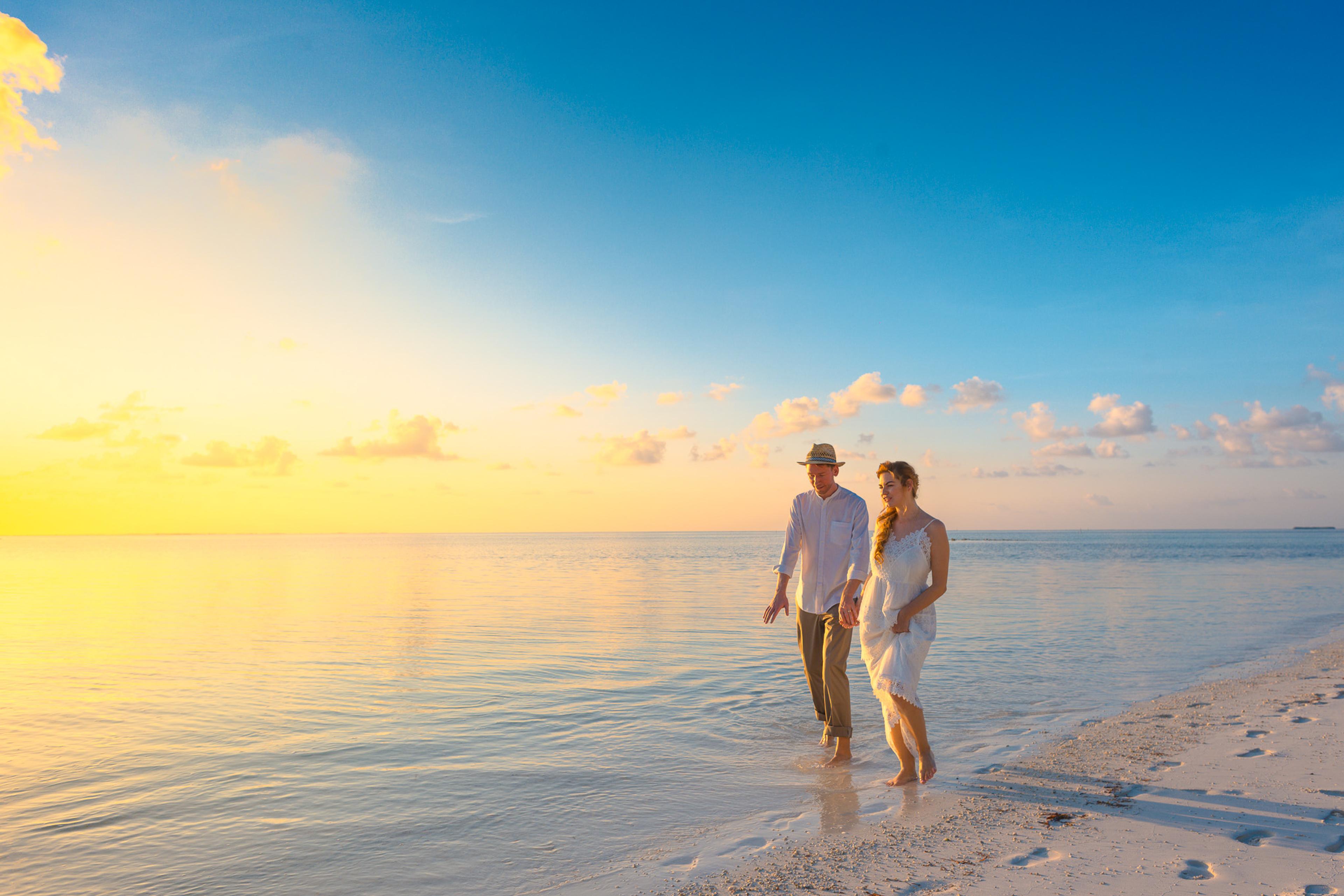夕方に白いトップスを着て海岸を歩くカップル