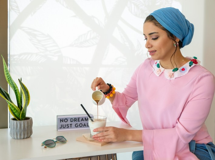 Woman Holding Ceramic Mug Pouring Liquid on Glass on the Table