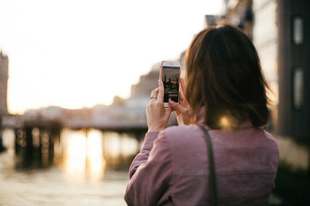 Woman Wearing Maroon Long-sleeved Shirt Holding Smartphone