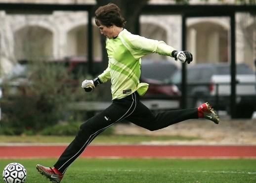 Man in Black Pants Playing Soccer during Daytime