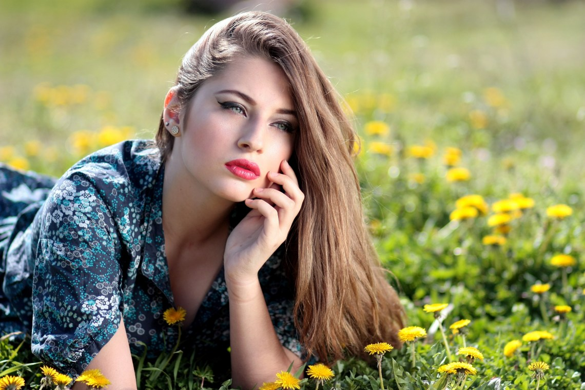 Girl Lying on Yellow Flower Field during Daytime