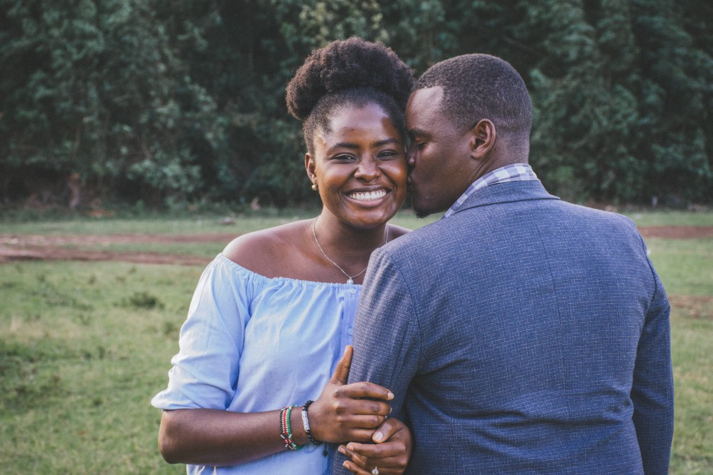 Man Kissing Left Cheek of Smiling Woman, in love