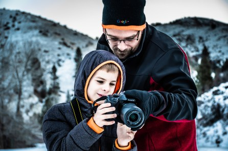 Man Standing Beside Boy While Holding Dslr Camera in Selective Focus Photography