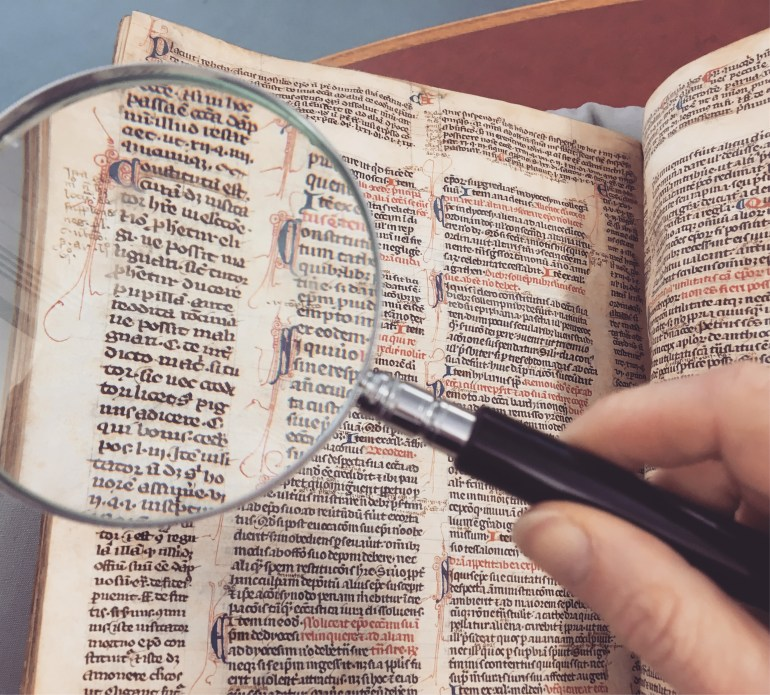 Person Holding Magnifying Glass Pointing on Book