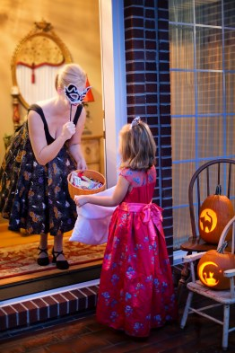 Woman Making Trick of Treat in Front of a Girl
