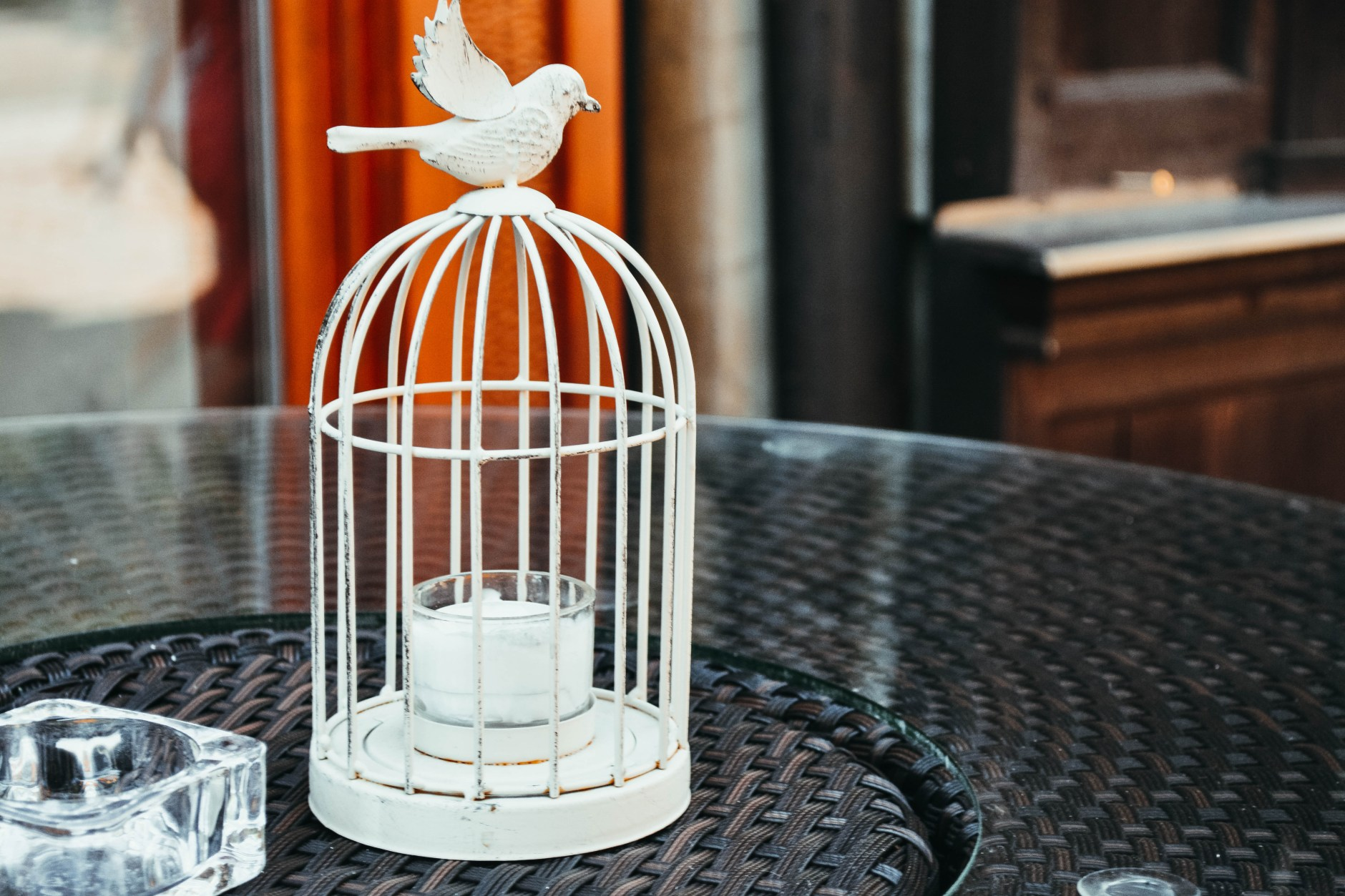 candle in a cage container placed on a table