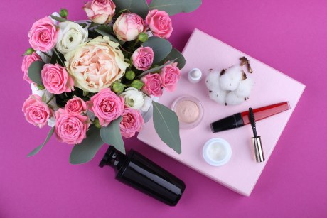 Top View Photography of Pink and White Rose Flowers in Vase Beside Assorted Cosmetics on Pink Surface