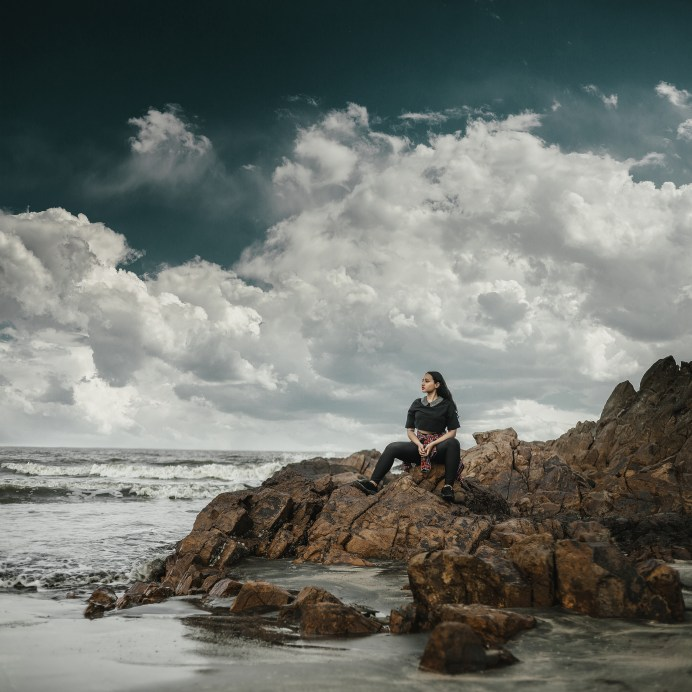 Photo of Woman Sitting on Rocks Near Beach Looking into the Distance