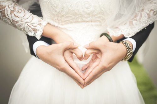 Bride and groom midsection, hands in shape of heart. wedding day