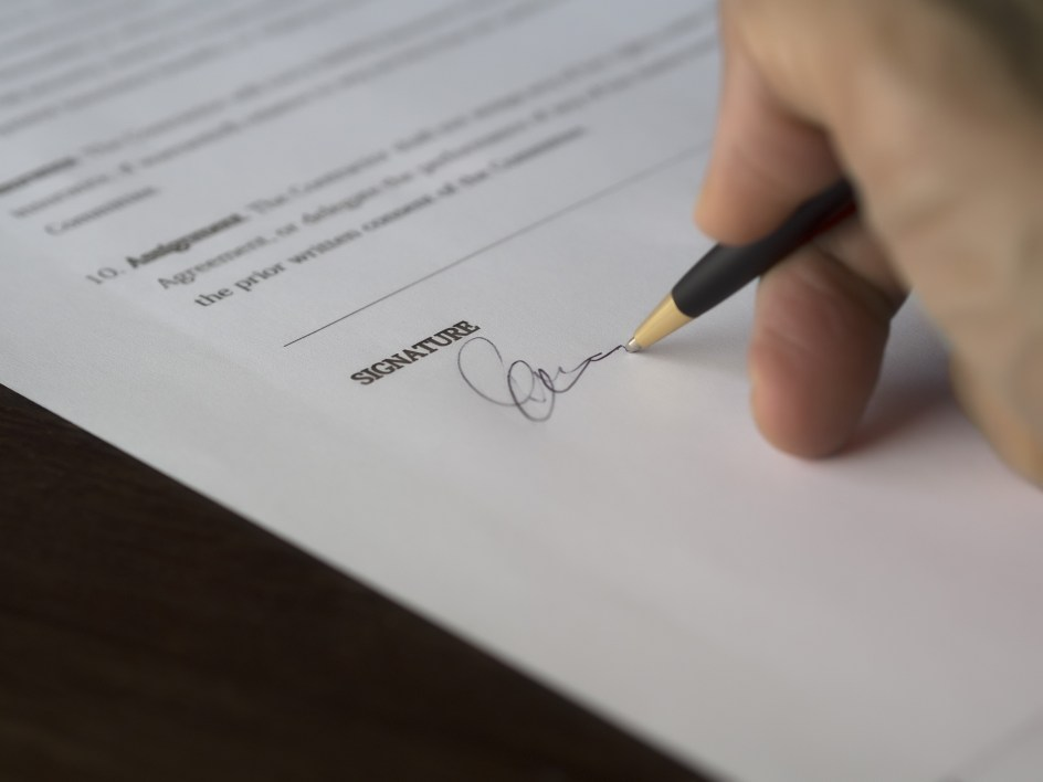 Selective Focus Photography of Person Signing on Paper