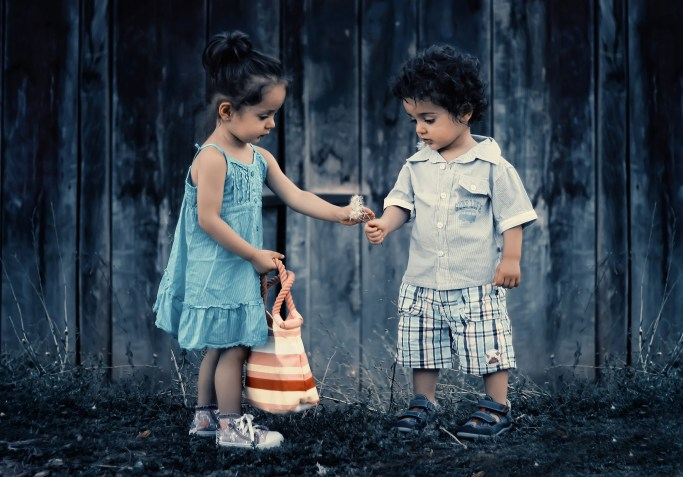 Boy and Girl Standing Near Wooden Wall