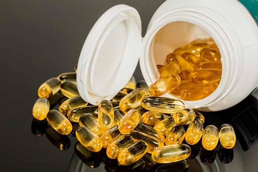 Vitamins Gel Capsules Inside and Outside Plastic Bottle
