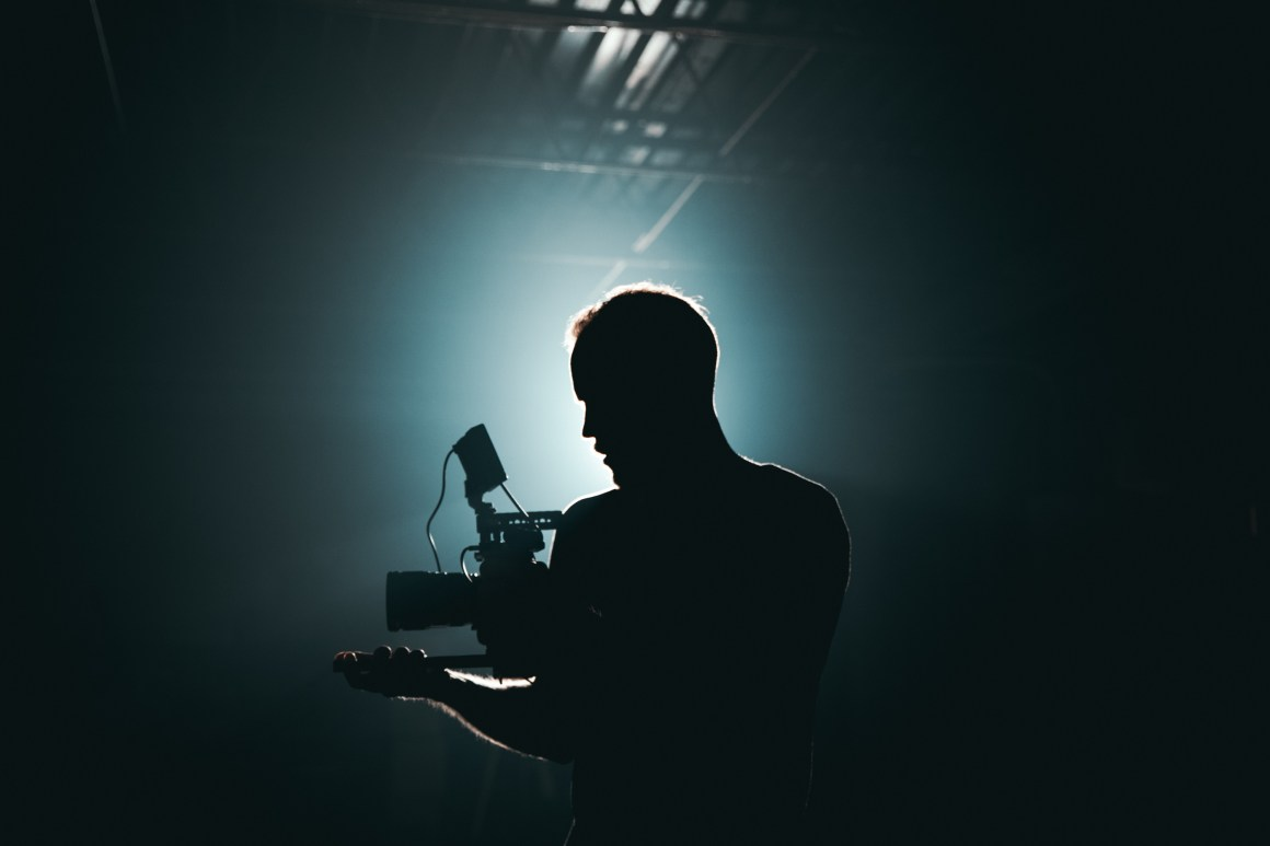Silhouette of Man Standing in Front of Microphone