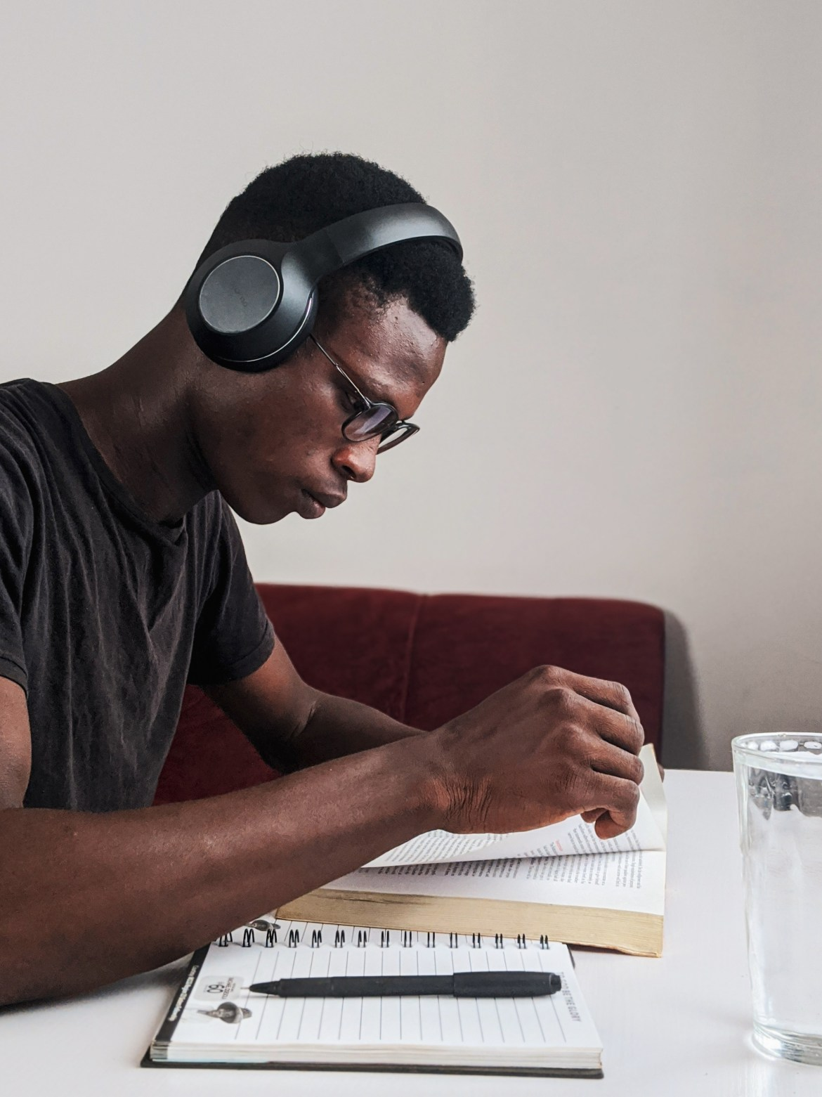Man Wearing Black Crew-neck T-shirt Using Black Headphones Reading Book While Sitting
