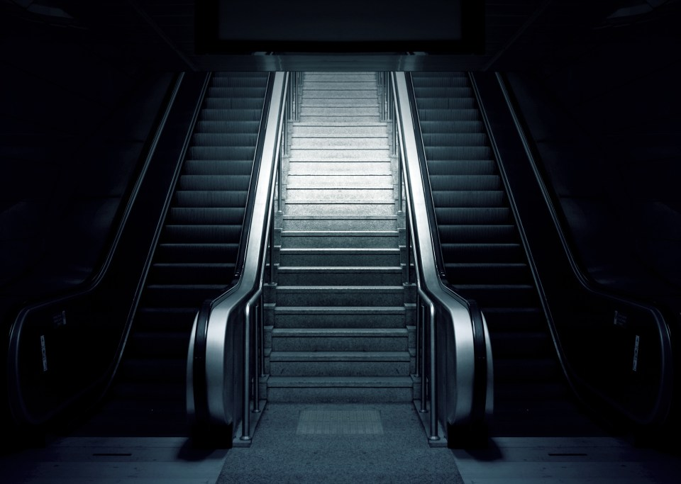 Grey and Black Escalator on Dimmed Place. Advice on taking the stairs and getting Fitness Success in 2019!