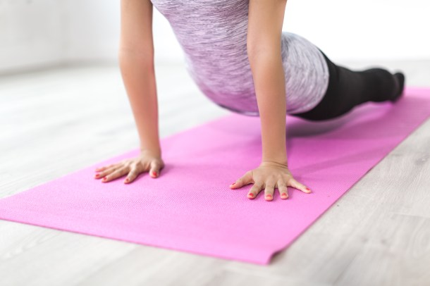 women stretching on pink yoga mat