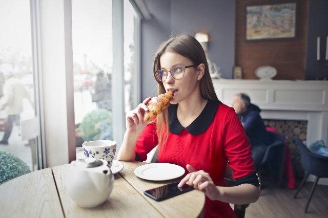 Woman Sitting on Wooden Chair Eating Bread