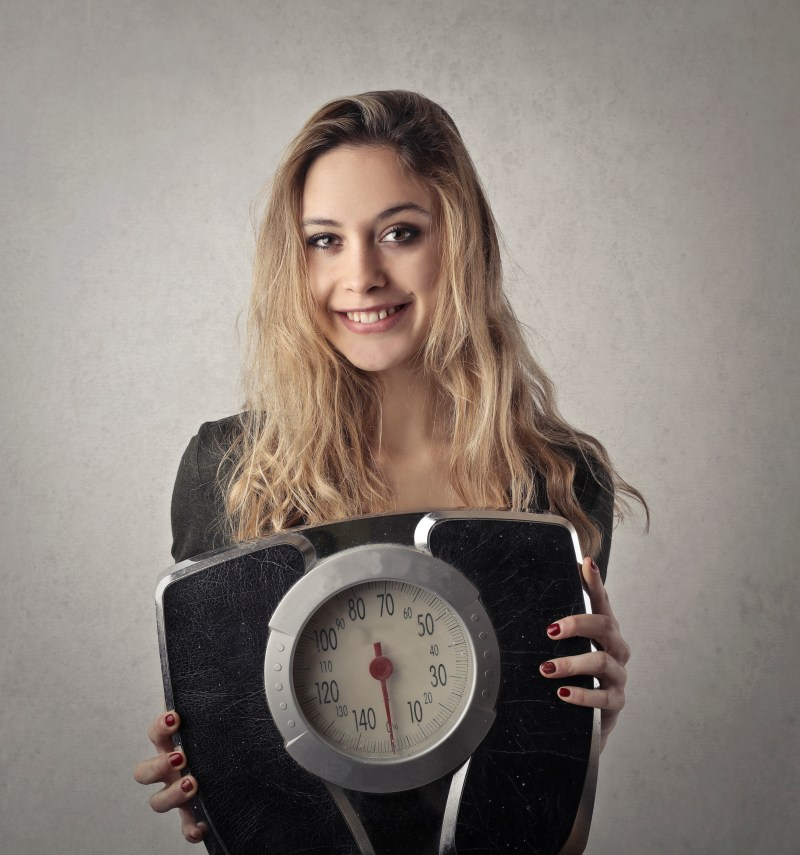Woman in Black Shirt Holding Black and Silver Weight Scale