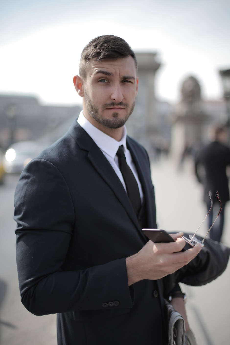 Man in Black Suit Holding Smartphone and Sunglasses