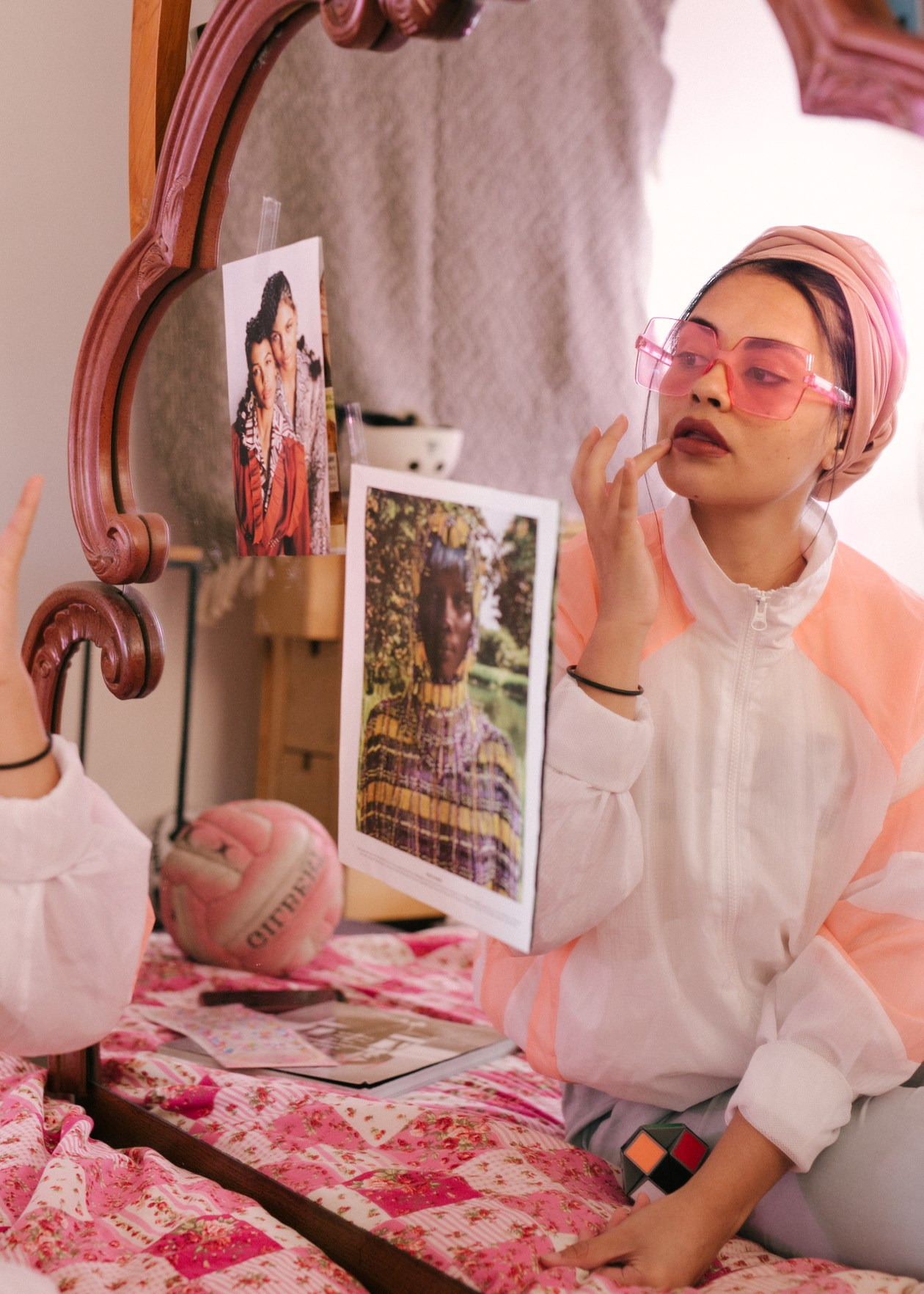 Young stylish female in eyeglasses and turban sitting on bed in bedroom and adjusting makeup while looking in mirror