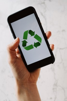Black smartphone with a recycling logo on the screen.