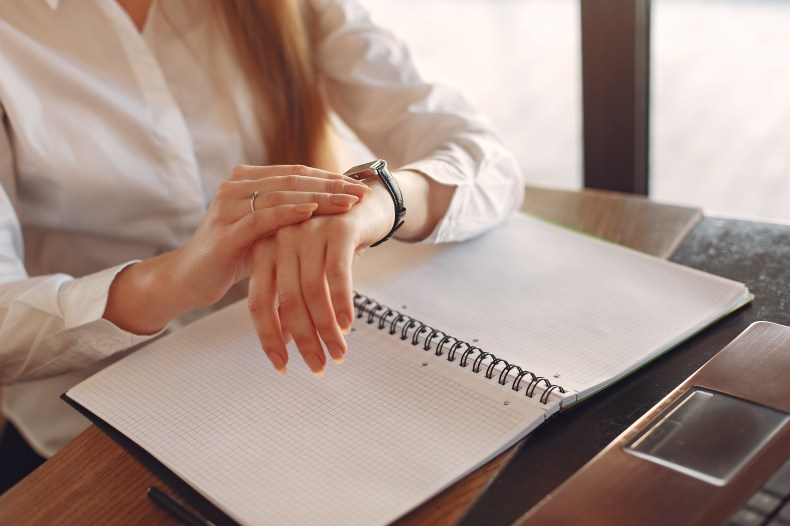 Faceless crop female entrepreneur checking time  while working with papers