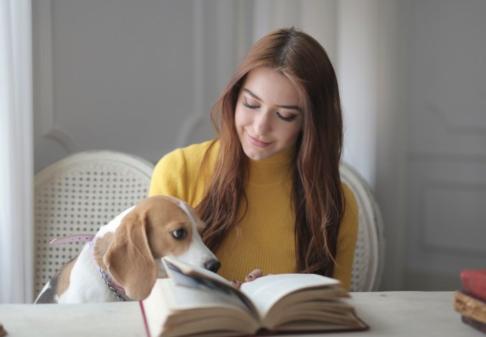 Happy woman in casual clothes with cute dog reading book