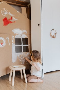 Young Girl Painting Cardboard House connecting art and happiness