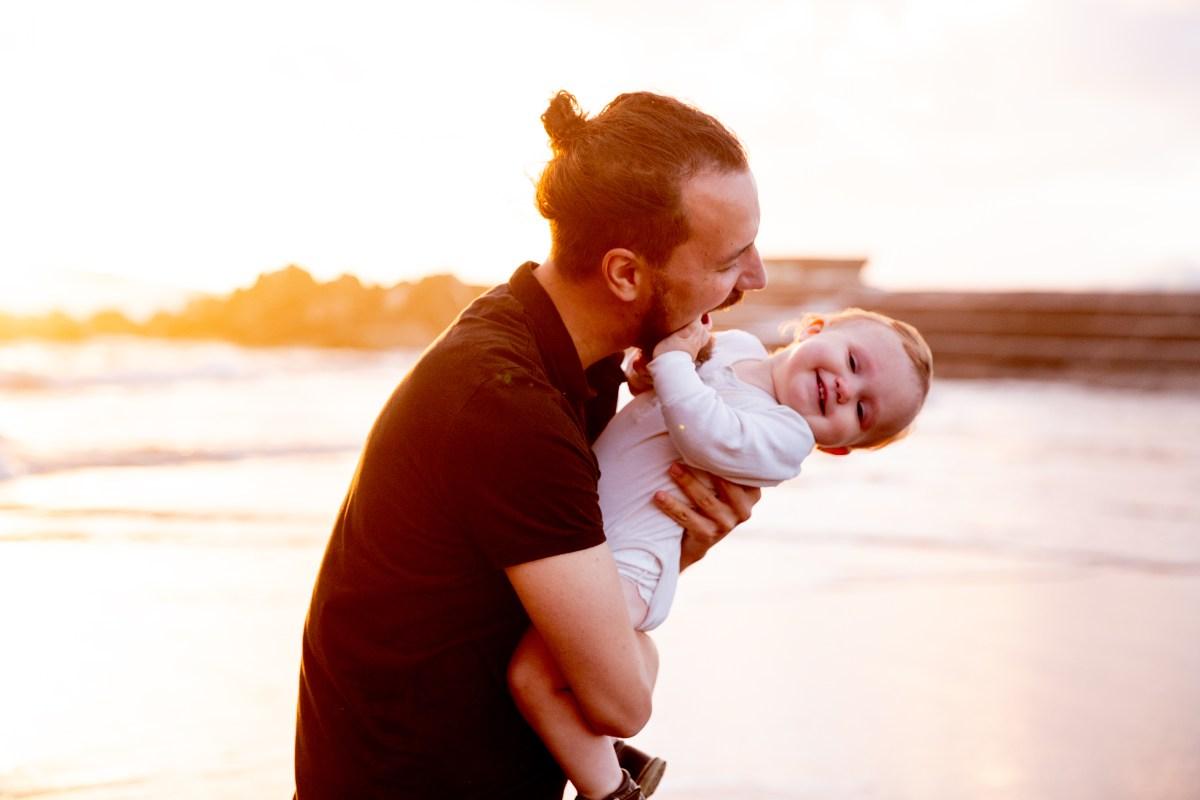Ayah dan Peringatan Hari Anak: Man in Black T-shirt Carrying Baby in White Onesie